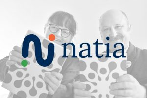 two people holding book with natia logo ontop